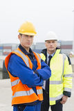 Portrait of confident worker standing with coworker in shipping yard Stock Photos