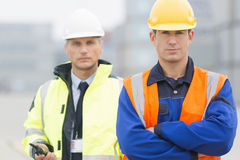 Portrait of confident worker standing with coworker in shipping yard Royalty Free Stock Photos