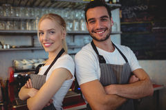 Portrait of confident workers at cafe. Portrait of confident workers standing with arms crossed at cafe Royalty Free Stock Images