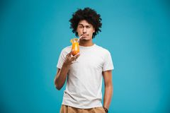 Portrait of a confident young african man. Drinking tropical cocktail isolated over blue background Royalty Free Stock Image