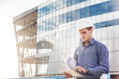 Portrait of confident young architect or chief engineer uses digital tablet at the construction site. Chief Construction with drawings manages the facility royalty free stock photo