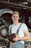 Portrait of a confident young auto mechanic holding a new air suspension system. Low-angle view portrait of a confident young auto mechanic holding a new air stock photo