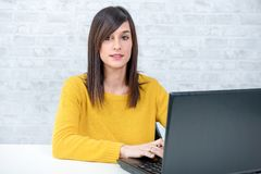 Confident young beautiful businesswoman with laptop at office Stock Photography