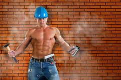 Portrait of confident young beautiful handyman with tools on the background wall. Stock Image