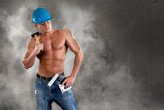 Portrait of confident young beautiful handyman with tools on the background wall. Stock Photo