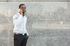 Portrait of a confident young black businessman talking on cell phone Royalty Free Stock Images