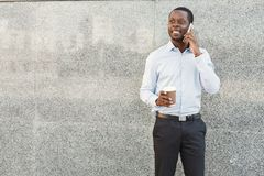 Portrait of a confident young black businessman talking on cell phone Stock Image