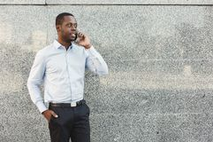 Portrait of a confident young black businessman talking on cell phone Royalty Free Stock Photography