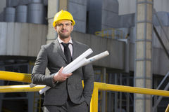 Portrait of confident young businessman holding blueprints outside industry Stock Photos