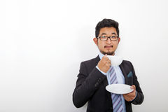 Portrait of confident young businessman holding coffee cup and plate over white background Royalty Free Stock Photography