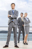Portrait of confident young businessman standing with coworkers on terrace against sky Stock Photos