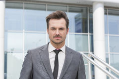 Portrait of confident young businessman standing outside office building Stock Photo