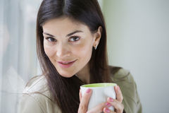 Portrait of confident young businesswoman with coffee cup in office Royalty Free Stock Photos