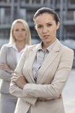 Portrait of confident young businesswoman with female colleague in background Stock Image