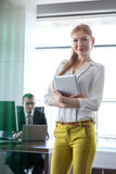Portrait of confident young businesswoman holding digital tablet with businessman in background at office.  Stock Photography