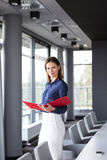 Portrait of confident young businesswoman holding file in conference room Stock Photography