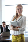 Portrait of confident young businesswoman holding tablet PC with businessman in background at office.  Stock Photos