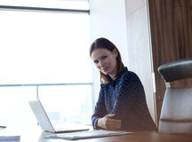 Portrait of confident young businesswoman with laptop at desk in office Royalty Free Stock Photo
