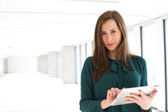 Portrait of confident young businesswoman using digital tablet in office Stock Photo
