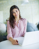 Portrait of confident young businesswoman using laptop at office table Royalty Free Stock Images