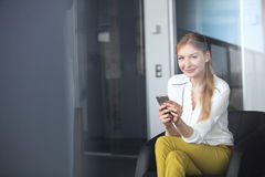 Portrait of confident young businesswoman using mobile phone on chair in office Royalty Free Stock Photography