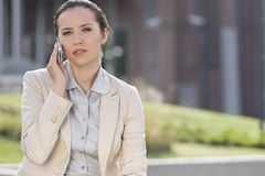 Portrait of confident young businesswoman using mobile phone outdoors Stock Photo