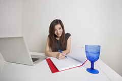 Portrait of confident young businesswoman writing on diary at office desk Royalty Free Stock Photos