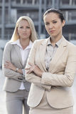Portrait of confident young businesswomen standing arms crossed outdoors Stock Image