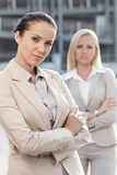 Portrait of confident young businesswomen standing arms crossed outdoors Stock Images