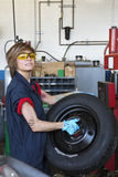 Portrait of a confident young female mechanic carrying tire in vehicle repair shop Royalty Free Stock Photography