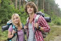 Portrait of confident young hiking couple in forest Royalty Free Stock Images