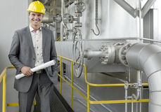 Portrait of confident young male architect holding blueprint by machinery in industry stock images