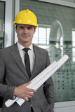Portrait of confident young male architect holding blueprints in industry Royalty Free Stock Photography