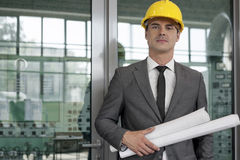 Portrait of confident young male architect holding rolled up blueprints in industry Royalty Free Stock Photo