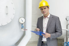 Portrait of confident young male inspector writing on clipboard in industry Stock Image