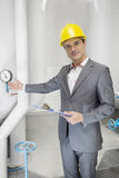 Portrait of confident young male manager with clipboard showing machine in industry Royalty Free Stock Photos