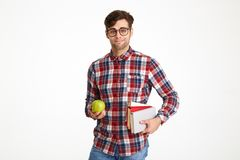 Portrait a confident young male student holding books. With green apple and looking at camera isolated over white background Stock Images