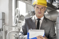 Portrait of confident young male supervisor writing on clipboard in industry Stock Photo