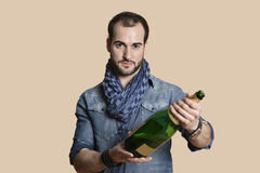 Portrait of a confident young man with champagne bottle over colored background Stock Photography