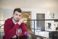 Portrait of confident young man drinking water from glass in cafe Royalty Free Stock Photography