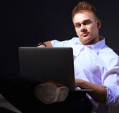 Portrait of confident young man with laptop standing over gray background Royalty Free Stock Images