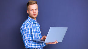 Portrait of confident young man with laptop standing over gray background Stock Photography