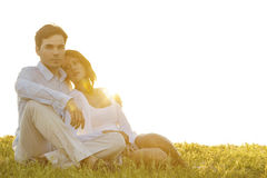 Portrait of confident young man sitting with girlfriend on grass against clear sky Royalty Free Stock Photography