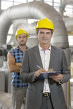 Portrait of confident young manager writing on clipboard with manual worker in background at industry Stock Image