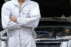 Portrait of confident young mechanic man in uniform with crossed arms and standing against car in open hood at the repair garage. Royalty Free Stock Image