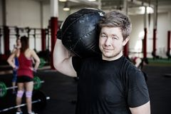 Man Carrying Medicine Ball On Shoulder In Gym Royalty Free Stock Photography
