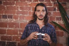 Portrait of confident young photographer holding camera against brick wall. At coffee shop Stock Photo