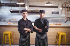 Portrait of confident young wait staff in black uniform standing with arms crossed at coffee shop. Portrait of confident young wait staff in black uniform Royalty Free Stock Images