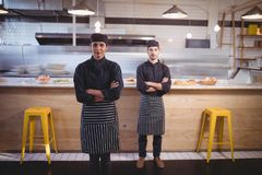 Portrait of confident young wait staff standing with arms crossed against counter. In coffee shop Stock Images