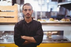Portrait of confident young waiter standing against counter Royalty Free Stock Image